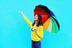 Happy smiling young woman holding colorful umbrella in autumn day looking up over colorful blue background Stock Photography