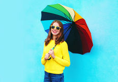 Happy smiling young woman holding colorful umbrella in autumn day over blue background wearing a yellow knitted sweater Royalty Free Stock Photo