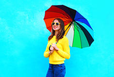 Happy smiling young woman holding colorful umbrella in autumn day over blue background wearing yellow knitted sweater Stock Photo