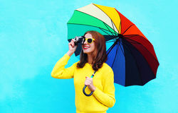 Happy smiling young woman holding colorful umbrella taking picture on vintage camera in autumn day over blue background. Wearing yellow knitted sweater Royalty Free Stock Photos