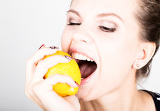 Happy smiling young woman holding fresh juicy lemons. Healthy eating, fruits and vegetables. Stock Photos