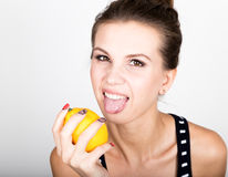 Happy smiling young woman holding fresh juicy lemons. Healthy eating, fruits and vegetables. Royalty Free Stock Photography