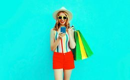 happy smiling young woman holding smartphone with shopping bags in colorful t-shirt, summer straw hat, sunglasses, red shorts stock images