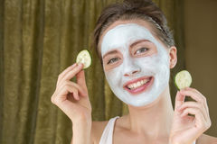 Happy smiling young woman holding two cucumbers near to her head stock image
