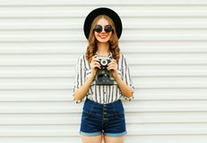 Happy smiling young woman holding vintage film camera in black round hat, shorts, white striped shirt on white wall. Background royalty free stock images