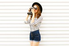 Happy smiling young woman holding vintage film camera in black round hat, shorts, white striped shirt on white wall. Background royalty free stock photos
