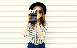 Happy smiling young woman holding vintage film camera in black round hat, shorts, white striped shirt on white wall. Background stock photography