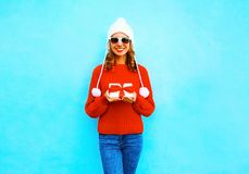 Happy smiling young woman holds gift box in hands. On a blue background Royalty Free Stock Image