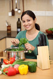 Happy smiling young woman in kitchen Stock Images