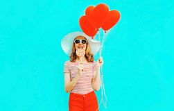 Happy smiling young woman with lollipop, red heart shaped air balloons in summer straw hat and shorts on colorful stock photo