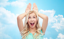 Happy smiling young woman making bunny ears Royalty Free Stock Image