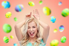 Happy smiling young woman making easter bunny ears royalty free stock photo