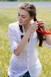 Happy smiling young woman making hair in braid on summer meadow Royalty Free Stock Images
