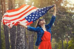 Happy smiling young woman with national american flag outdoors Royalty Free Stock Photo