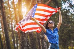 Happy smiling young woman with national american flag outdoors Royalty Free Stock Photography