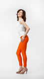 Happy smiling young woman in orange pants posing on neutral back Stock Images