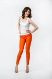Happy smiling young woman in orange pants posing on neutral back Stock Photo