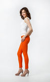 Happy smiling young woman in orange pants posing on neutral back Stock Image