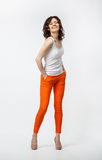Happy smiling young woman in orange pants posing on neutral back Royalty Free Stock Photos