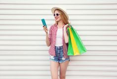 Happy smiling young woman with phone, holding colorful shopping bags in summer round straw hat, checkered shirt, shorts on white royalty free stock photo