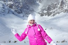 Happy smiling young woman in pink ski jacket preparing to throw. A snow ball with snow covered mountain in the background royalty free stock photography