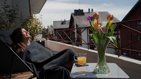 Happy smiling young woman in plaid enjoying spring sun on terrace. Bouquet of colorful tulips and cup of orange juice. Stand next on table 4k stock video footage