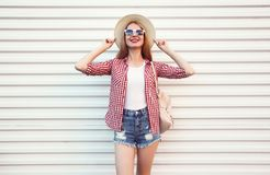 Happy smiling young woman posing in summer round straw hat, checkered shirt, shorts on white wall. Background royalty free stock photography