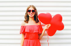 Happy smiling young woman in red dress and sunglasses with air balloons heart shape over white Royalty Free Stock Photo