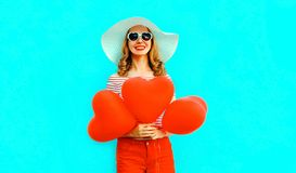 Happy smiling young woman with red heart shaped air balloons in summer straw hat and shorts on colorful blue royalty free stock photography