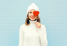 Happy smiling young woman with red lips holds lollipop heart wearing knitted hat sweater over blue Stock Photos