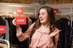 Happy smiling young woman with red sale sign. stock photography