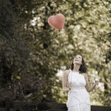 Happy Smiling Young Woman with a Red Shaped Heart Balloon. Happy Smiling Young Woman Standing with a Red Shaped Heart Balloon Outdoors Stock Image