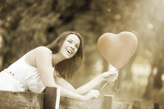 Happy Smiling Young Woman with a Red Shaped Heart Balloon. Happy Smiling Young Woman Standing with a Red Shaped Heart Balloon Outdoors Stock Photos