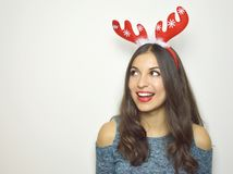 Happy smiling young woman with reindeer horns on her head looks your product on white background. Copy space. Happy smiling young woman with reindeer horns on Royalty Free Stock Photos