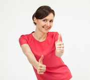 Happy smiling young woman showing thumbs up sign Stock Photo