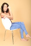 Happy Smiling Young Woman Sitting in a White Chair Relaxing Stock Image