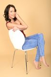 Happy Smiling Young Woman Sitting in a White Chair Relaxing Royalty Free Stock Photos
