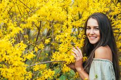 Happy smiling young woman with spring flowers at garden Stock Photos