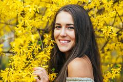 Happy smiling young woman with spring flowers at garden Stock Image