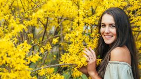 Happy smiling young woman with spring flowers at garden Stock Photo