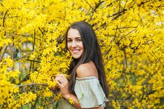 Happy smiling young woman with spring flowers at garden Royalty Free Stock Photo