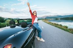Happy smiling young woman stay near the cabriolet car on the mou. Ntain road Royalty Free Stock Images