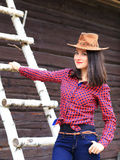 Happy smiling young woman in stetson. On wooden background Stock Photo