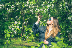 Happy smiling young woman in sunglasses and a knitted jacket enjoying spring flowers in the garden Royalty Free Stock Images