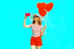 Happy smiling young woman taking selfie picture by phone with red heart shaped air balloons in summer straw hat stock images