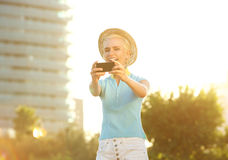 Happy smiling young woman taking selfie portrait outside Stock Images