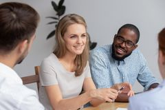 Happy smiling young woman talking with coworkers at work. Happy smiling young blond women talking with diverse male coworkers having break at work. Excited royalty free stock photos