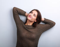 Happy smiling young woman in warm sweater looking up with hands Royalty Free Stock Photography