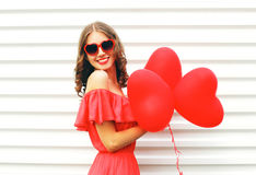 Happy smiling young woman wearing red dress and sunglasses with air balloons heart shape over white Royalty Free Stock Images