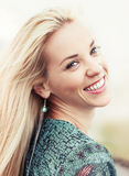 Happy smiling young woman with wind into the hair Royalty Free Stock Photography